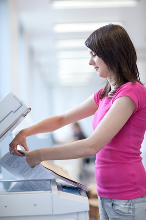 pretty young woman using a copy machine (shallow DOF; color toned image) Stock Photo - 9926321