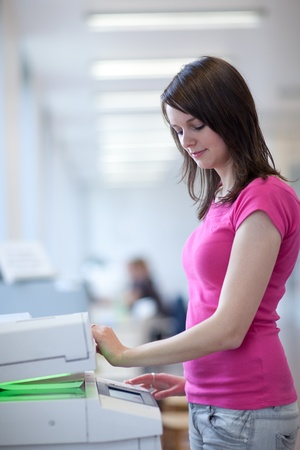 pretty young woman using a copy machine (shallow DOF; color toned image) photo