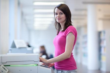 copier: mooie jonge vrouw met behulp van een kopieermachine