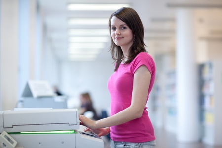 pretty young woman using a copy machine  photo