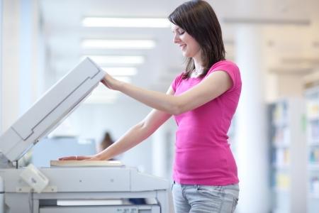 mooie jonge vrouw met behulp van een kopieermachine (ondiepe DOF; kleur getinte afbeelding) Stockfoto