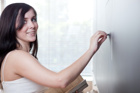 pretty young college student drawing on the chalkboardblackboard during a math class photo