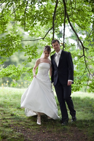 young wedding couple - freshly wed groom and bride posing outdoors on  their wedding day photo