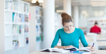 higher: pretty young college student in a library  Stock Photo