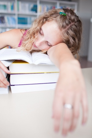 pretty female tired/exhausted/sleepy college student taking a nap  in a library Stock Photo - 9926055