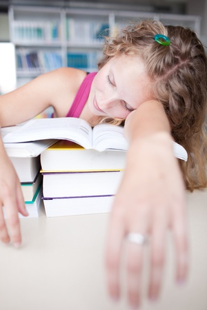 pretty female tiredexhaustedsleepy college student taking a nap  in a library photo