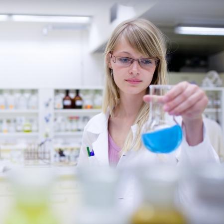 bata de laboratorio: Retrato de un mujer investigador llevar a cabo investigaciones en un laboratorio de qu�mica (color en tonos imagen; DOF superficial)