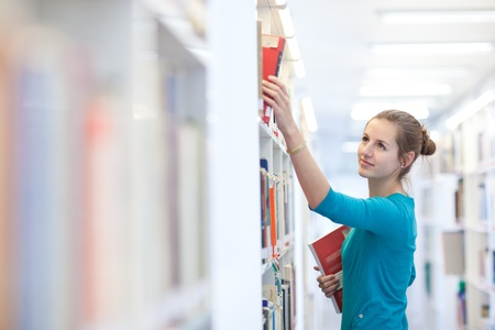 college student: pretty young college student in a library  Stock Photo
