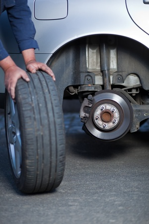 mecánico de cambiar una rueda de un coche moderno (DOF superficial; imagen en tonos de color)