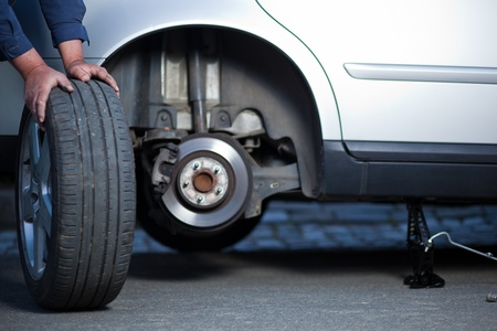 mecánico de cambiar una rueda de un automóvil moderno (DOF superficial; imagen de tonos de color)
