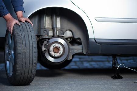 llantas: mec�nico de cambiar una rueda de un autom�vil moderno (DOF superficial; imagen de tonos de color)