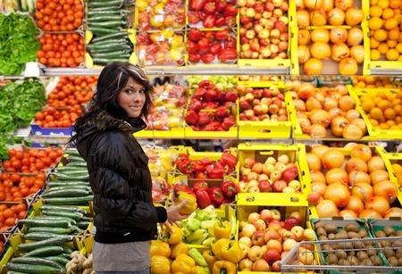 abarrotes: Hermosa mujer joven compra frutas y verduras en un departamento de producci�n de un supermercadotienda