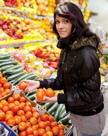 Beautiful young woman buying fruits and vegetables at a produce department of a supermarketgrocery store photo