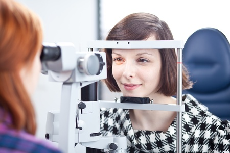 optometry concept - pretty young woman having her eyes examined by an eye doctor (color toned image) photo
