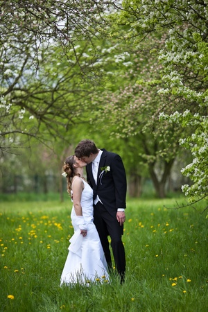 young wedding couple - freshly wed groom and bride posing outdoors on their wedding day Stock Photo - 9939818