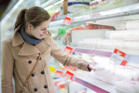 beauty store: pretty young woman buying groceries (eggs) in a supermarketmallgrocery store (color toned image; shallow DOF) Stock Photo