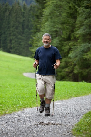 active handsome senior man nordic walking outdoors on a forest path, enjoying his retirement Stock Photo - 9959953