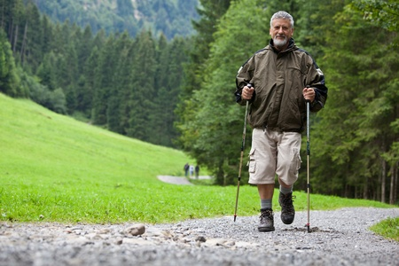 active handsome senior man nordic walking outdoors on a forest path, enjoying his retirement Stock Photo - 9959952