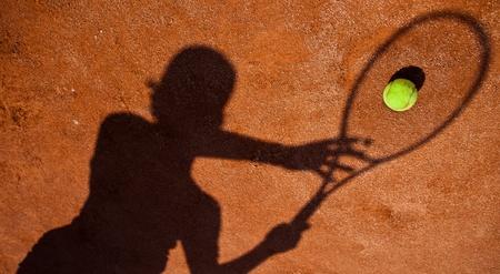 backhand: sombra de un tenista en acci�n en una cancha de tenis