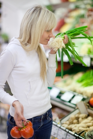 Beautiful young woman shopping for fruits and vegetables in produce department of a grocery store/supermarket (shallow DOF; color toned image) Stock Photo - 9939993