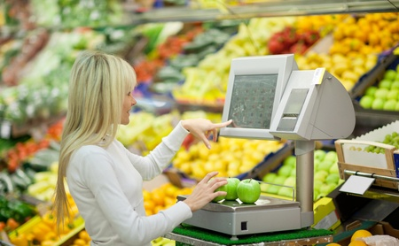 Beautiful young woman shopping for fruits and vegetables in produce department of a grocery storesupermarket photo