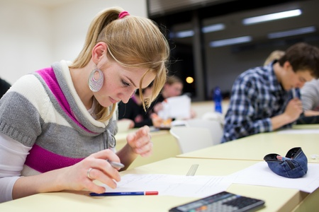 pretty female college student sitting an exam in a classroom full of students Stock Photo - 9960483