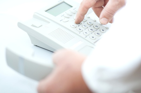 conference call: man making a phone call, dialing the number (white telephone on white background)