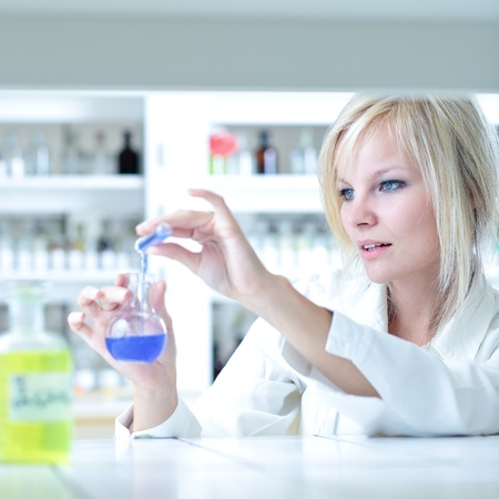 Closeup of a female researcher holding up a test tube and a retort and carrying out some experiments Stock Photo - 9960495