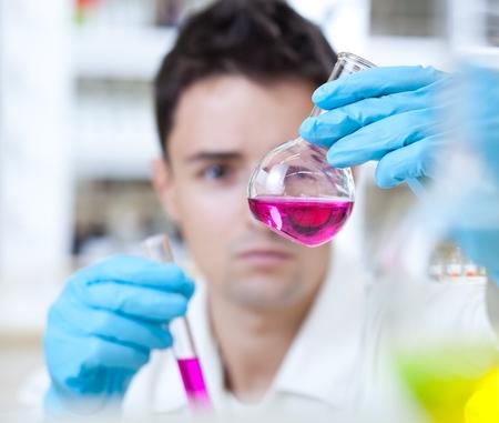 vaso de precipitado: joven investigador masculino llevar a cabo investigaciones cient�ficas en el laboratorio Foto de archivo