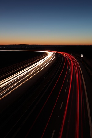 Night highway (Cars in a rush moving fast on a highway (speedway) at the nightfall photo
