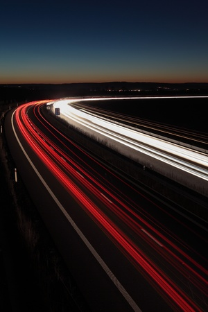 proceed: Night highway (Cars in a rush moving fast on a highway  (speedway) in the UK at the nightfall