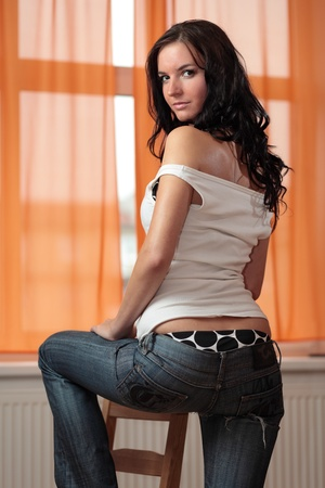 attractive young brunette posing home in her kitchen on a chair photo