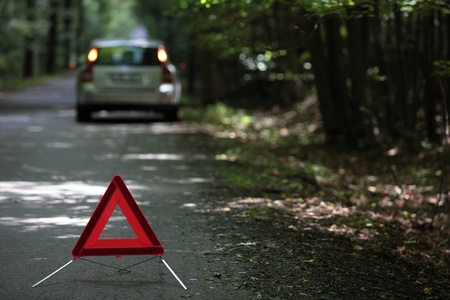inconvenient: broken down car with warning triangle behind it waiting for assistance to arrive (shallow depth of field, the focus is on the triangle, the car is left out of focus)