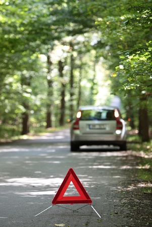 broken down - car with warning triangle behind it waiting for assistance to arrive (shallow depth of field, the focus is on the triangle, the car is left out of focus) photo