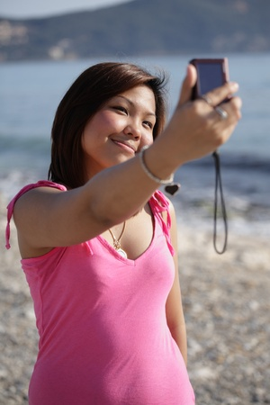 pic  picture: Pretty young asian woman taking a self-portrait while outdoors on a beach on a summer day Stock Photo