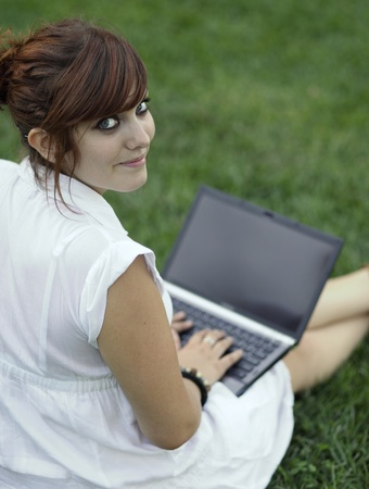 Pretty young woman working on a laptop computer outdoors, looking at the camera photo