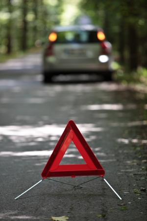 damaged vehicles: broken down car with warning triangle behind it waiting for assistance to arrive (shallow depth of field, the focus is on the triangle, the car is left out of focus)