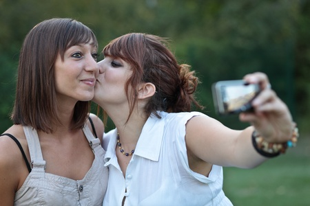 two young caucasian female friends taking autoportraits of themselves kissing, having fun photo