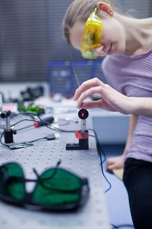 physics: female scientist doing research in a quantum optics lab (color toned image)