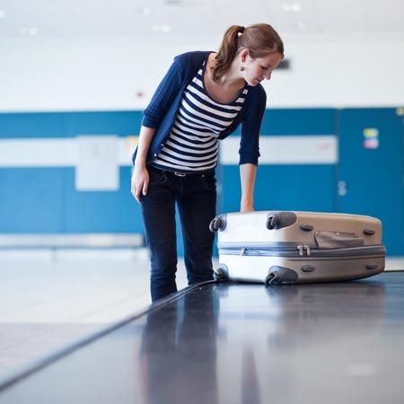 gente aeropuerto: De recogida de equipajes en el aeropuerto - bastante joven tomando su maleta de la cinta transportadora de equipaje (imagen a color entonado)