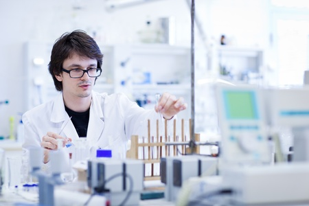 chemical laboratory: young male researcher carrying out scientific research in a lab