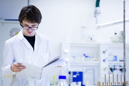 analyze: young male researcher carrying out scientific research in a chemistry lab