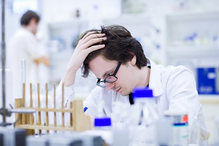 young male researcher carrying out scientific research in a chemistry lab  photo