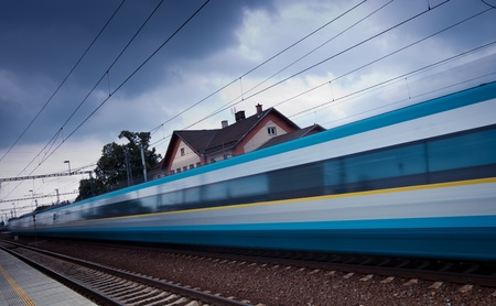 convey: Fast train passing by (motion blur is used to convey movement; color toned image)