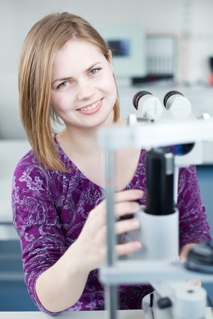 optometry concept - portrait of a young pretty optometrist using slit lamp (color toned image) Stock Photo - 9959857