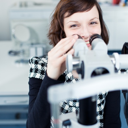 optometry concept - portrait of a young pretty optometrist using a slit lamp photo