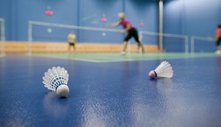 shuttle: badminton - badmintonbanen met spelers concurreren; shuttles op de voorgrond (ondiepe DOF; kleurenafbeelding afgezwakt) Stockfoto