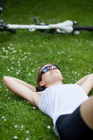 pretty female biker having a rest while on a biking trip Stock Photo - 9948293