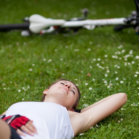 rest and relaxation: pretty female biker having a rest while on a biking trip