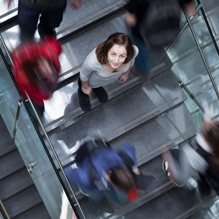rush: At the universitycollege - Students rushing up and down a busy stairway - confident pretty young female student looking upwards (color toned image)